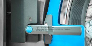 Промышленные стиральные машины для прачечных и химчисток. Индустриальная прачечная. На фото ручка дверцы загрузки выгрузки белья профессиональной стиральной машины JENSEN JWE 110/250.