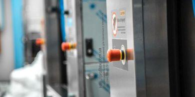 Промышленные и профессиональные стиральные машины. Индустриальная прачечная. На фото аварийная кнопка остановки профессиональной стиральной машины JENSEN JWE 110/250.